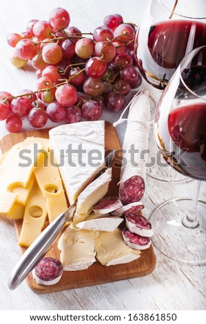 Red wine in  glass with grapes, camembert, emmentaler