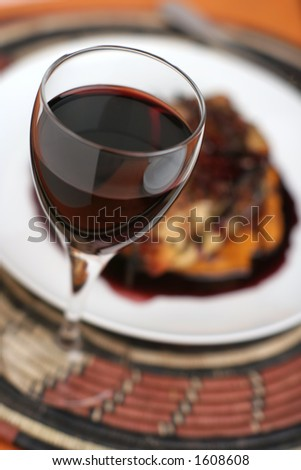 Red wine in glass with shallow depth of field in front of a meal with a rich red wine sauce.