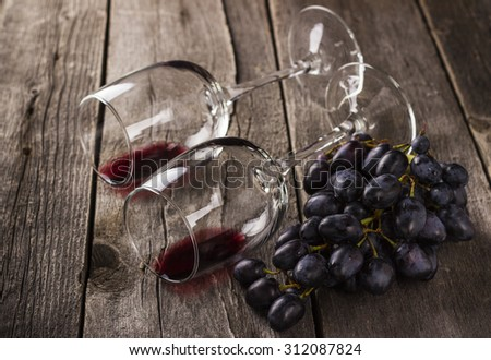 Red wine in glasses and grapes cluster on a wooden background - stock photo