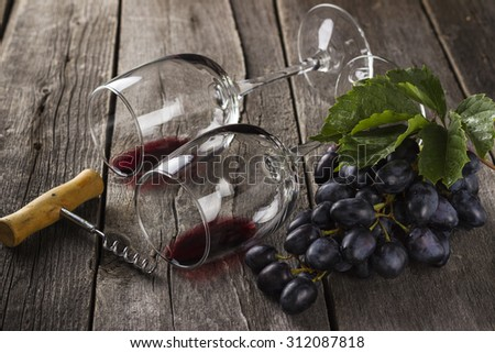 Red wine in glasses, corkscrew and cluster of grapes on a wooden background - stock photo