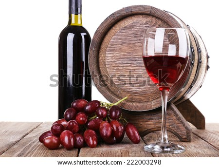 Red wine in goblet and in bottle, grapes and barrel on wooden table on white background - stock photo