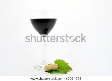 red wine in goblet with cork and vine leaf