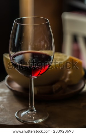 Red wine in wine glass with cheese. Selective Focus. Focus on the front of the rim of the wine glass