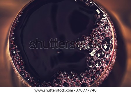 Red wine in wineglass against wooden background, focus on a center - stock photo