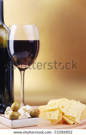 Red wine in wineglass cheese and olives - stock photo