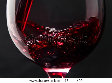 Red wine in wineglass on a black background - stock photo