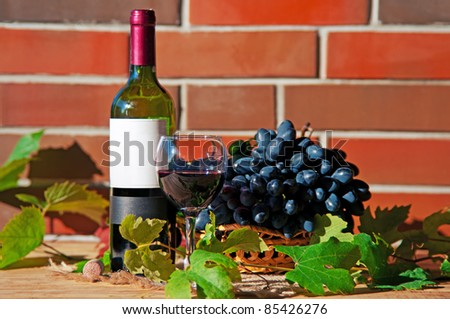Red wine in wineglass with grape and leaves near brick wall