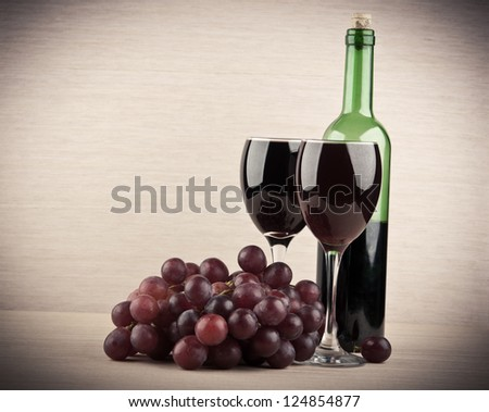 red wine into glasses on wooden background