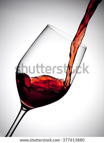 Red wine is poured into a wine glass, making a large curving splash - stock photo