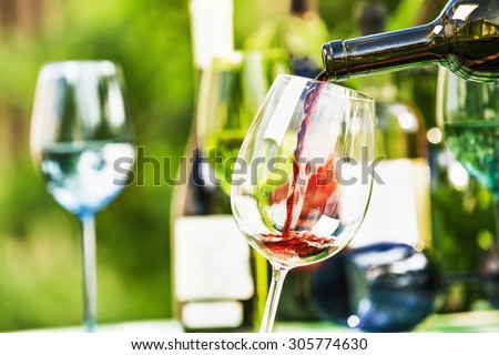 Red wine on a background of colored bottles - stock photo