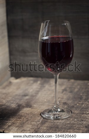 Red wine on old wooden table - stock photo