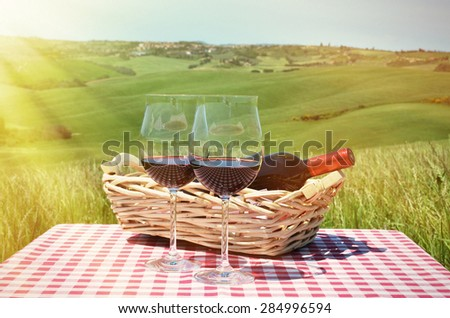 Red wine on the chequered cloth against Tuscan landscape. Italy - stock photo
