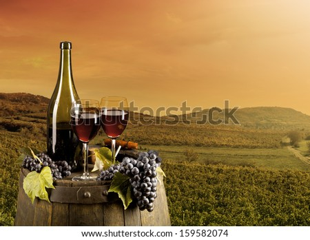 Red wine on wooden keg with vineyard on background