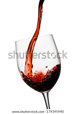 Red wine poured in a glass isolated on white - stock photo