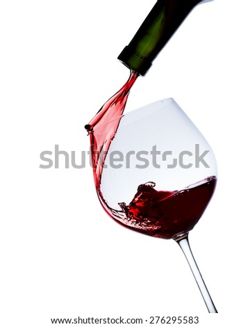 Red wine poured in a glass isolated on white