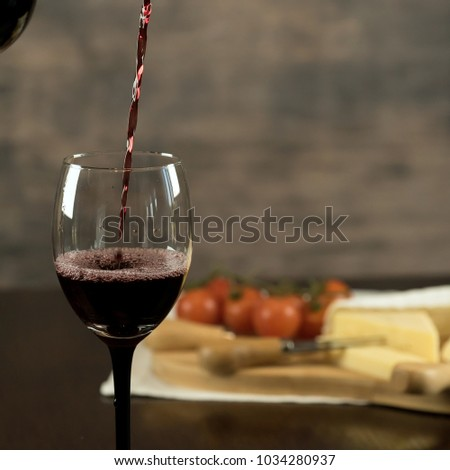 Red wine poured into a glass with cheese board