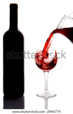 Red wine pouring down into a wine glass and a wine bottle - stock photo