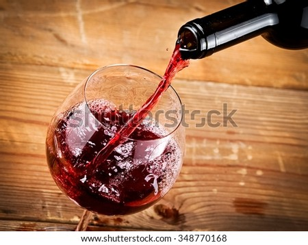 Red wine pouring from a bottle, close up - stock photo
