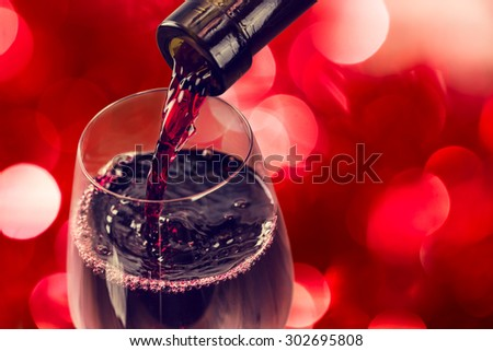 Red Wine pouring in glass and Bottle on the bokeh background - stock photo