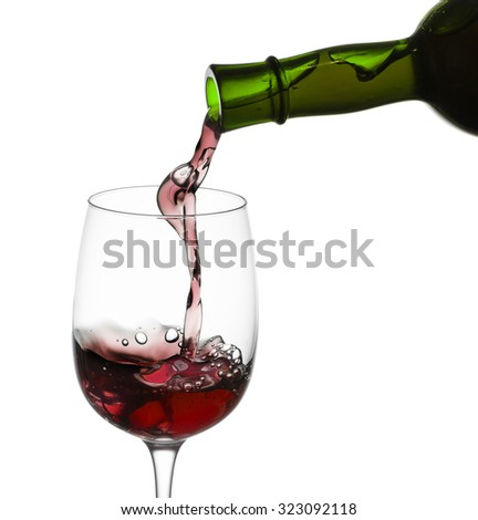 red wine pouring in glass from a bottle isolated on white background