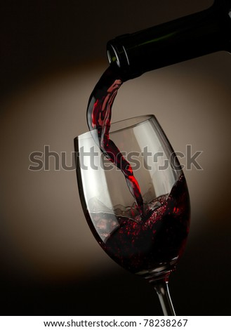Red wine pouring in glass over dark background - stock photo