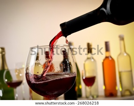 Red wine pouring into a glass from a bottle - stock photo