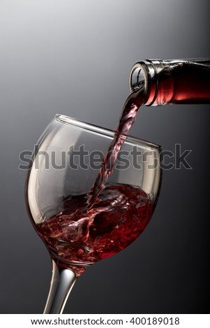 Red wine pouring into a glass isolated on black background
