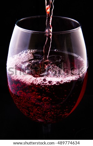 Red wine pouring into a glass on black background