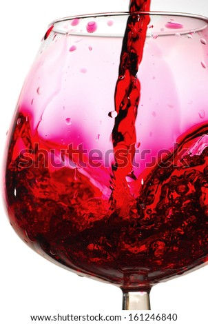 Red wine pouring into a glass, studio isolated on white background
