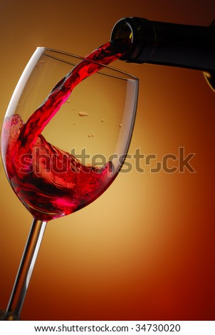 Red wine pouring into a glass with abstract background