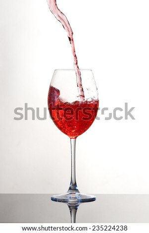 Red wine pouring into a glass with bubbles with white background - stock photo