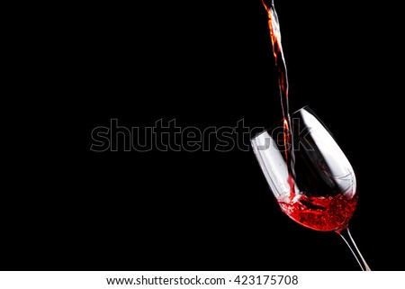 Red wine pouring into a wine glass. Isolated on black background.  - stock photo