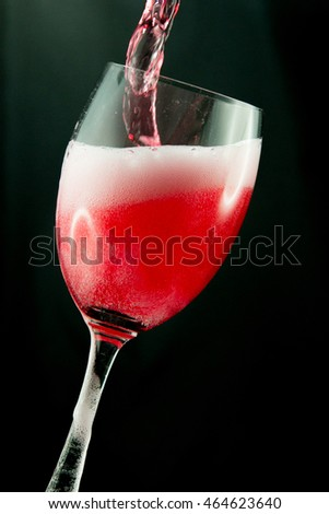 Red wine pouring into a wine glass. Isolated on black background.