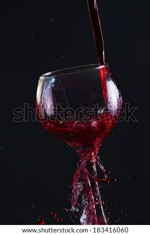 Red Wine Pouring into glass black isolated - stock photo