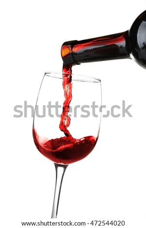 Red wine pouring into glass on white background