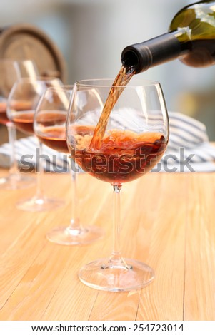 Red wine pouring into wine glass, close-up - stock photo