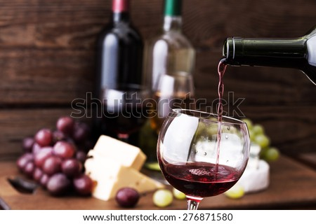 Red wine pouring into wine glass, close-up. Flat mock up for design. - stock photo
