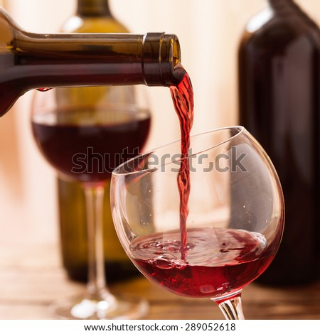 Red wine pouring into wine glass, close up. Flat mock up for design. - stock photo