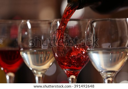 Red wine pouring into wine glass, closeup - stock photo