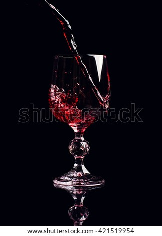 Red wine pouring into wine glass with splash, isolated on black