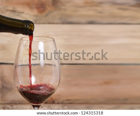 Red Wine Pouring on a wood background - stock photo