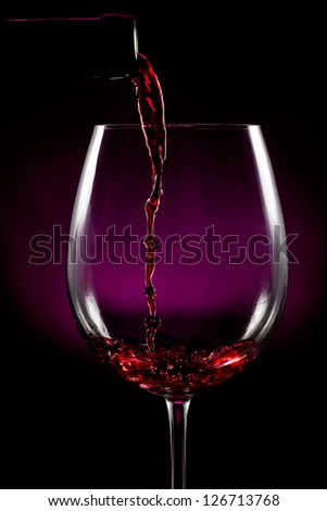 Red wine pouring on black - stock photo
