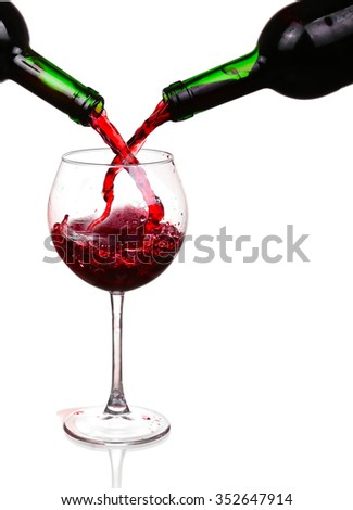Red wine pouring on white background - stock photo