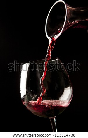 Red wine splash on a glass on black background. - stock photo