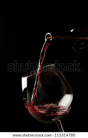 Red wine splash on a glass on black background.