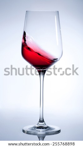 Red wine splashing in the elegant wine glass on gray background
