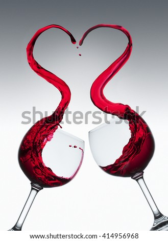 Red wine splashing out of two glasses in heart shape