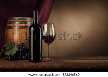 Red wine tasting with bottle, wineglass, barrel and grape on the cellar wooden table, red drape on background, still life - stock photo