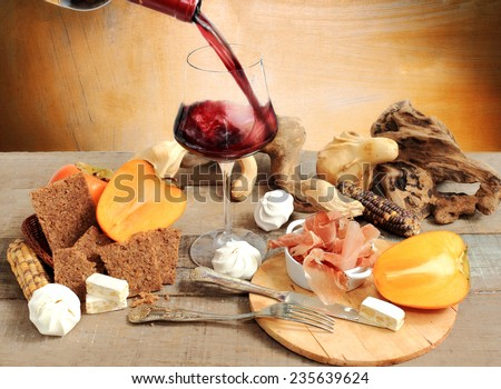 red wine tasting with persimmon, Parma ham, meringue, cereal bread and winter decorations - stock photo