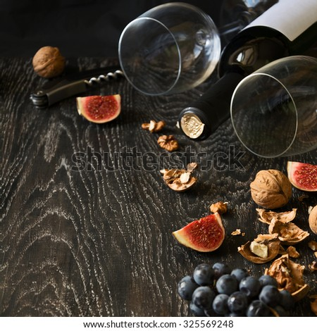 Red wine, two wineglass with walnuts, grapes and figs on dark wooden background - stock photo